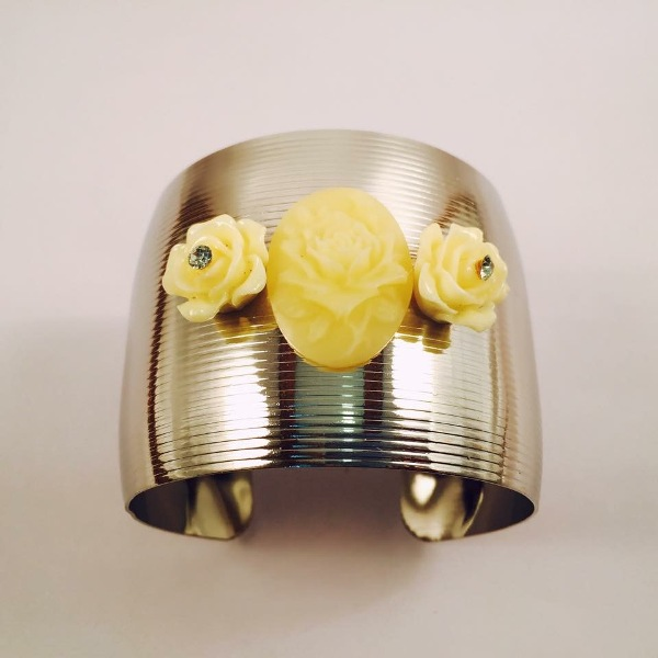 Silver toned cuff bracelet with off white flowers