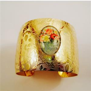 Gold toned cuff bracelet with a multi flower cobochon